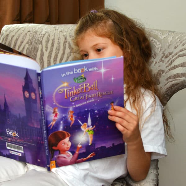 child reading tinkerbell book