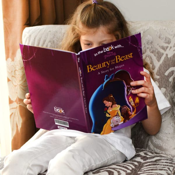 child reading beauty and the beast book